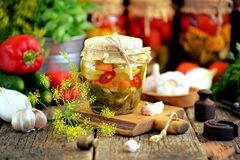 Homemade marinated zucchini with chili, dill, carrots, garlic and onions in a jar on an old wooden background. Rustic style. stock photography