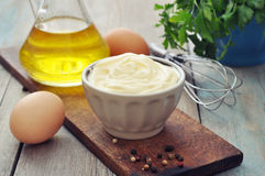 Homemade mayonnaise. In bowl with oil, eggs and spice on wooden background Stock Image