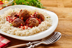 Homemade Meal of Saucy Meatballs on a Bed of Rice. Close Up Still Life of Homemade Meatballs in Tomato Sauce on a Bed of Fluffy Seasoned Rice Served in Modern Stock Photo