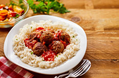 Homemade Meal of Saucy Meatballs on a Bed of Rice. High Angle Still Life of Homemade Meatballs in Tomato Sauce on a Bed of Fluffy Seasoned Rice Served in Modern Royalty Free Stock Photos