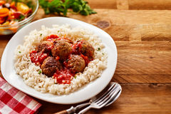 Homemade Meal of Saucy Meatballs on a Bed of Rice. High Angle Still Life of Homemade Meatballs in Tomato Sauce on a Bed of Fluffy Seasoned Rice Served in Modern Royalty Free Stock Photography