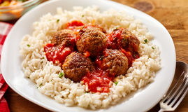 Homemade Meal of Saucy Meatballs on a Bed of Rice. High Angle Still Life of Homemade Meatballs in Tomato Sauce on a Bed of Fluffy Seasoned Rice Served in Modern Stock Photo