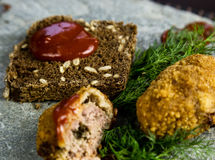 Homemade meat cutlets with parsley, ketchup and bread on white plate Stock Photos