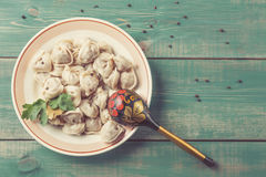 Homemade Meat Dumplings russian pelmeni with laurel leaf, parsley on plate and green wooden background with pepper and old russian. Wooden spoon. Top view and Royalty Free Stock Images