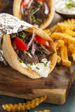 Homemade Meat Gyro with French Fries. Homemade Meat Gyro with Tzatziki Sauce, tomatos and French Fries royalty free stock image