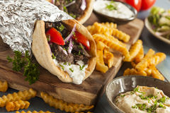 Homemade Meat Gyro with French Fries. Homemade Meat Gyro with Tzatziki Sauce, tomatos and French Fries royalty free stock photo