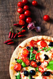 Homemade Meat Pizza with Pepperoni Sausage, Bacon and cherries. Tomatoes on a wooden table royalty free stock photo
