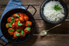 Homemade meatballs in tomato. Meatballs in tomato sauce with boiled riced and parsley Stock Photos