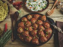 Homemade meatballs in tomato sauce. Frying pan on a wooden surface, rice with vegetables, pasta royalty free stock photos