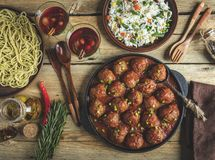 Homemade meatballs in tomato sauce. Frying pan on a wooden surface, rice with vegetables, pasta.  royalty free stock image