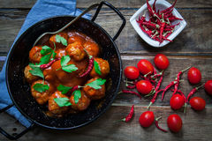 Homemade meatballs in tomato. Meatballs in tomato sauce with parsley and red hot chili pepper Stock Photo