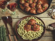 Homemade meatballs in tomato sauce with pasta on a plate. Frying pan on a wooden surface royalty free stock photo