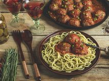Homemade meatballs in tomato sauce with pasta on a plate. Frying pan on a wooden surface stock photography