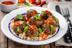 Homemade meatballs with wild rice, mint, green onions and chili sauce. On wooden table royalty free stock images