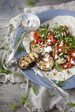 Homemade mediterranean flatbread with grilled eggplants, roasted tomatoes, wild fennel herb and yogurt on plate Stock Image