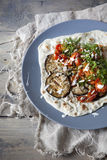 Homemade mediterranean flatbread with grilled eggplants, roasted tomatoes, wild fennel herb and yogurt on plate Stock Photo
