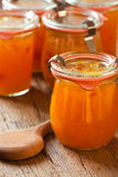 Homemade melon jam in a preserving jar. With a wooden spoon on old wooden table Royalty Free Stock Image