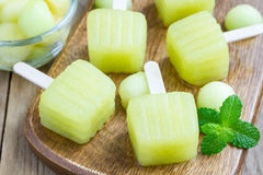 Homemade melon popsicles on a wooden background Royalty Free Stock Photography