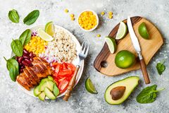 Homemade Mexican chicken burrito bowl with rice, beans, corn, tomato, avocado, spinach. Taco salad lunch bowl. Homemade Mexican chicken burrito bowl with rice stock photo