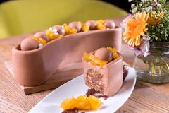 Homemade milk chocolate and chestnuts cake - milk chocolate mousse, pineapple marmalade, crispy base with hazelnuts and royalty free stock photography