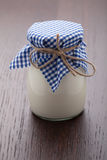 Homemade milk yogurt in glass pot on wooden table Royalty Free Stock Photo
