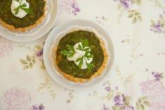 Homemade mini spinach and ricotta tarts on a white decorative na Royalty Free Stock Photo