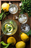 Homemade mint lemonade served with fresh lemons and ice over wooden background, top view, copy space Royalty Free Stock Photo