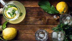 Homemade mint lemonade served with fresh lemons and ice over wooden background, top view, copy space Stock Photography
