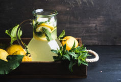 Homemade mint lemonade served with fresh lemons and ice over wooden background, top view, copy space Royalty Free Stock Photos