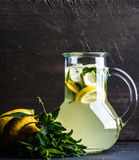 Homemade mint lemonade served with fresh lemons and ice over wooden background, top view, copy space Stock Images