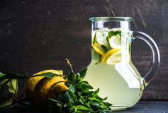 Homemade mint lemonade served with fresh lemons and ice over wooden background, top view, copy space Stock Photo