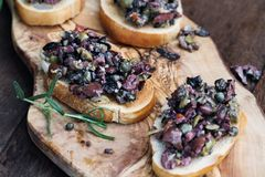 Prepared Tapenade on Toasted Bread. Homemade mixed Olive Tapenade made with garlic, capers, olive oil, Kalamata, black and green olives spread over toasted bread royalty free stock images