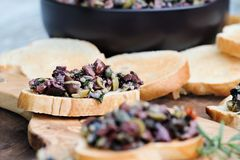 Fresh Tapenade on Toasted Bread. Homemade mixed Olive Tapenade made with garlic, capers, olive oil, Kalamata, black and green olives spread over toasted bread royalty free stock image