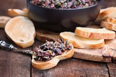 Mixed Olive Tapenade on Toasted Bread. Homemade mixed Olive Tapenade made with garlic, capers, olive oil, Kalamata, black and green olives spread over toasted royalty free stock photo