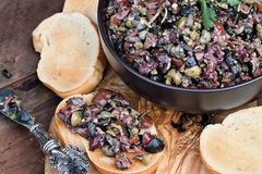 Tapenade Spread on Toasted Bread. Homemade mixed Olive Tapenade made with garlic, capers, olive oil, Kalamata, black and green olives spread over toasted bread stock images