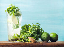 Homemade Mojito cocktail in tall glass with bunch of mint, brown sugar and limes Royalty Free Stock Images