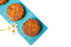 Homemade moon cake on bamboo mat and daisy on white background Royalty Free Stock Images