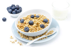 Homemade muesli, bowl of blueberries and glass of milk on white Stock Images