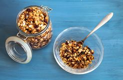 Homemade muesli in a plate on a blue background, healthy breakfast of oatmeal muesli, nuts, seeds and dried fruits stock photography