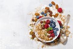 Homemade muesli with yogurt and berries on white table, top view. Horizontal Royalty Free Stock Image