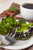 Fresh muffins with spinach, desiccated coconut, chocolate glaze and cup of coffee Stock Photo