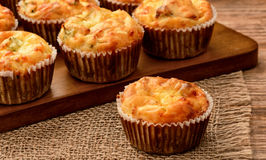 Homemade muffins with chicken and cheese on brown wooden board. Stock Photos