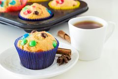 Homemade Muffins with colorful chocolate chips in dark blue paper case and a cup of black tea. White background. Front view stock image
