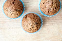 Homemade muffins on the kitchen table. Sweet homemade muffins on the kitchen table in blue pastry case Stock Photos