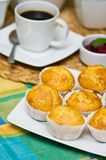 Homemade muffins. Still life image of tasty homemade muffins arranged on colorful tablecloth with coffee cup in the background Stock Photo