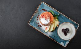 Homemade muffins with yogurt, blueberry, apple and jam in plate on dark stone background. Healthy breakfast.  royalty free stock images