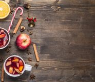 Homemade mulled wine with apple, orange, cinnamon, cloves and other ingredients have been laid out around on  wooden rustic backg Stock Photo