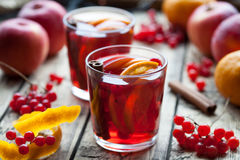 Homemade mulled wine or sangria with orange and apple slices, cranberries, cinnamon, anise on wooden table. royalty free stock image