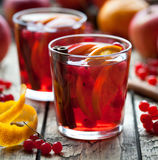 Homemade mulled wine or sangria with orange and apple slices, cranberries, cinnamon on wooden table. Square format. Stock Photo
