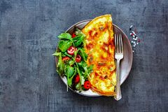 Mushroom omelette and salad. Homemade mushroom omelette with salad on plate over dark concrete copy space background. Healthy food concept. Flat lay, top view stock images
